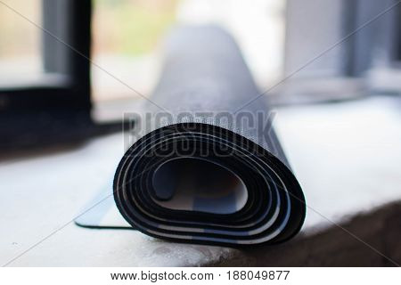 a rolled-up yoga Mat rests on a white background