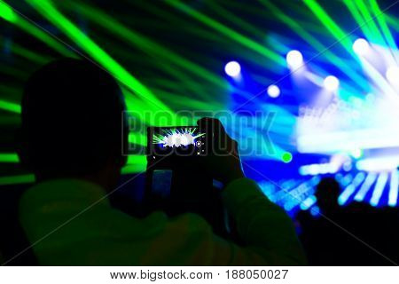 Man taking photo video by mobile phone of silhouettes crowd party concert music happy