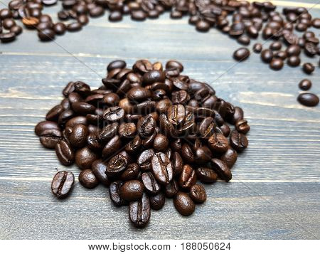 Closed-up coffee bean piles on dark wooden table