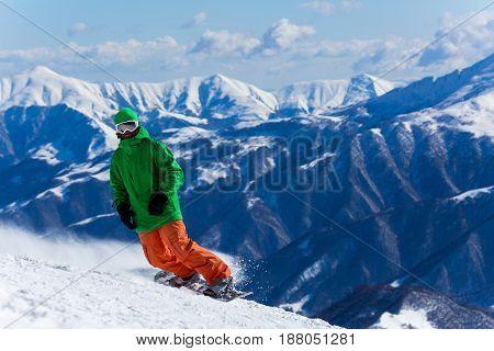 Male Snowboarder Snowboarding On Fresh Snow On Ski Slope On Sunny Winter Day In The Ski Resort In Ge