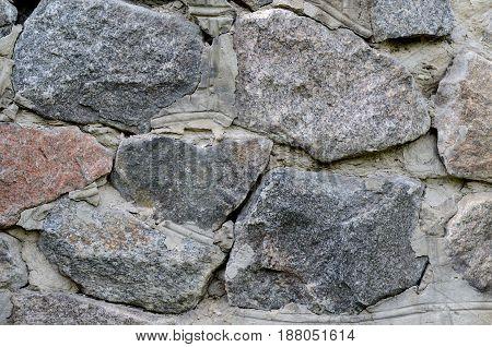 Old stone wall made of huge granite. Grunge design backdrop