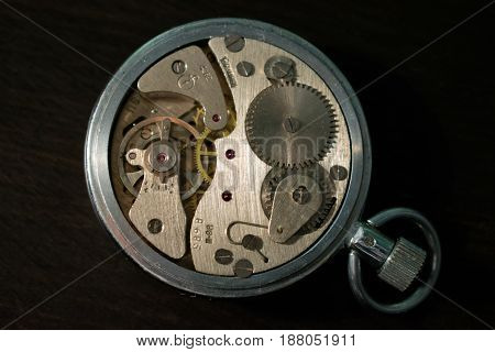 Old mechanism of pocket watches on a dark background of the desktop.
