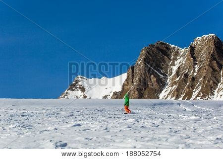 Male Snowboarder Snowboarding On Fresh Snow On Ski Slope On Sunny Winter Day In The Ski Resort In Ge
