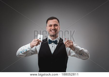 Handsome confident man holding cards looking at camera. Studio shot on gray background. Two Aces. Emotions happy