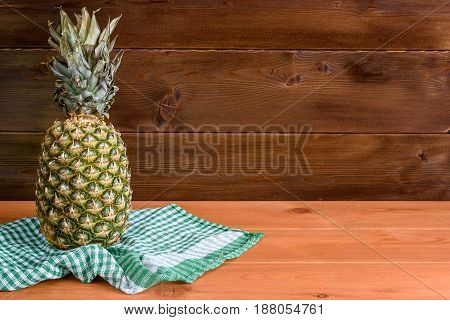 A Ripe Pineapple Lies On A Green Towel On A Wooden Table And A Wooden Background