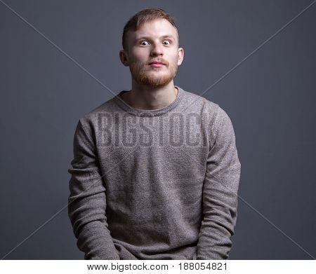 Portrait of beard surprised man on gray background