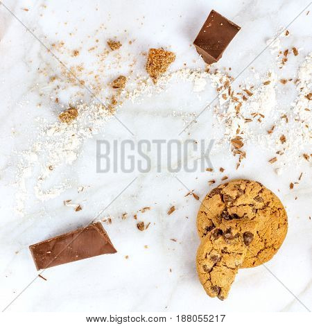 The process of making chocolate chips cookies. Overhead shot of biscuits with grated chocolate, cane sugar, and flour, forming frame for copy space, square photo