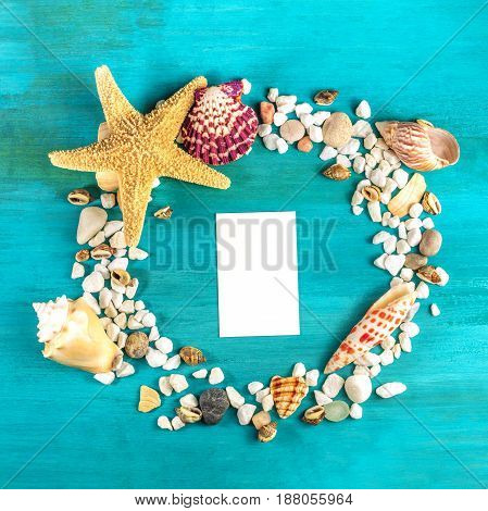 An overhead photo of a sea star, sea shells, and pebbles forming a frame on a vibrant turquoise background, with a business card inside. A square design template for a summer vacation banner