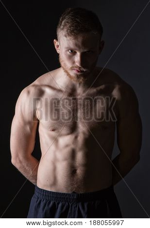 Bearded man with muscular torso on black background