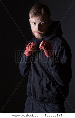 Fighter man wearing black tracksuit on black background