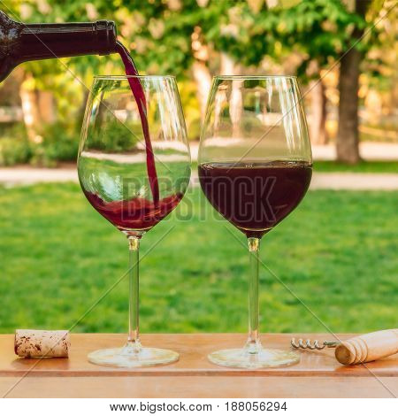 Red wine poured from a bottle into a glass at a picnic, with a cork and a corkscrew, with green grass in the blurred background, on a sunny day, square photo