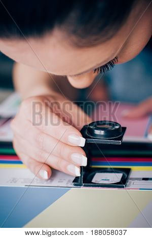 Worker In Printing And Press Centar Uses A Magnifying Glass