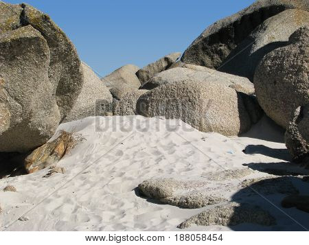 FROM CAMPS BAY  CAPE TOWN, SOUTH AFRICA, BEACH SAND IN FORE GROUND, WITH HUGE BOULDERS IN THE BACK GROUND 24kiuy
