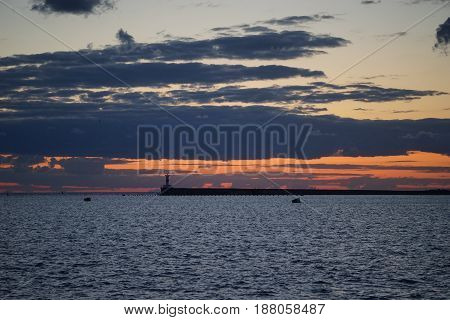 Sunset in the sea Bay on the payroll of the dark sky and Cape with a shining lighthouse