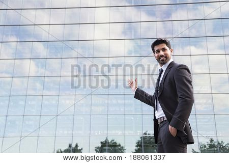 Arabic smiling businessman or worker in black suit with tie and shirt with beard standing in front of an office building on green grass in summer day and showing with his hand on glass building.