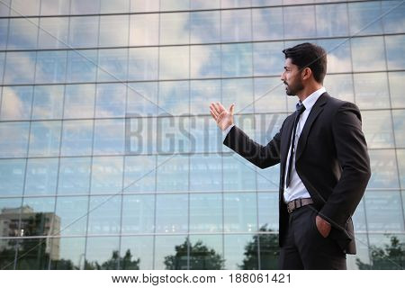 Arabic serious businessman or worker in black suit with tie and shirt with beard standing in front of an office building on green grass in summer day and showing with his hand on glass building.