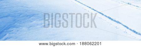 Abstract blue winter background. Tracks on snow.