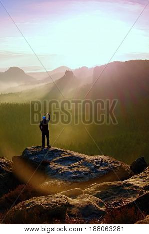 Man Takes Photos With Smart Phone On Peak Of Rock Empire. Dreamy Fogy Landscape, Spring Orange In A
