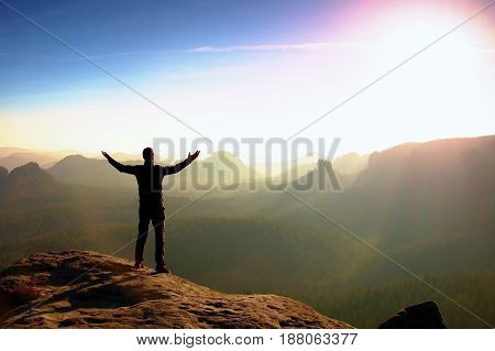 Hiker In Black. Gesture Of Triumph. Tall Tourist On The Peak Of Sandstone Rock In National Park Saxo