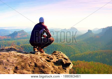 Young Man In Black Sportswear Is Sitting On Cliff Edge And Looking To Misty Valley Bellow