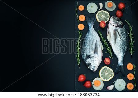 Fresh raw uncooked dorado fish with lemon, herbs, oil, vegetables and spices, top view