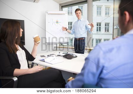 Confident businessman gesturing while giving presentation to colleagues in office