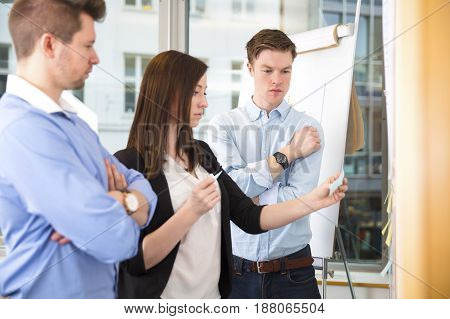 Male and female business coworkers with adhesive notes standing in office