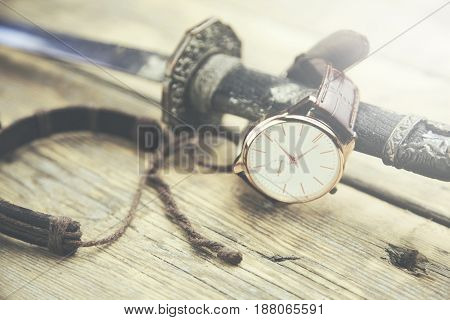 man elegant watch bracelet and a sword on wooden table