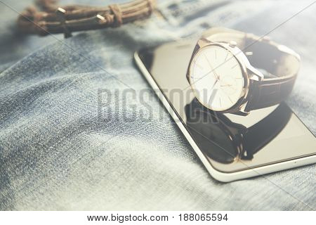 man watch and phone on the jeans