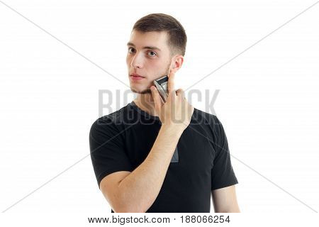 handsome young strong guy in a black t-shirt and looks toward shaves his beard close-up isolated on white background
