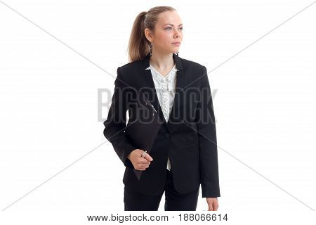 a serious young beautiful business woman standing in a black suit and holding a Tablet is isolated on a white background