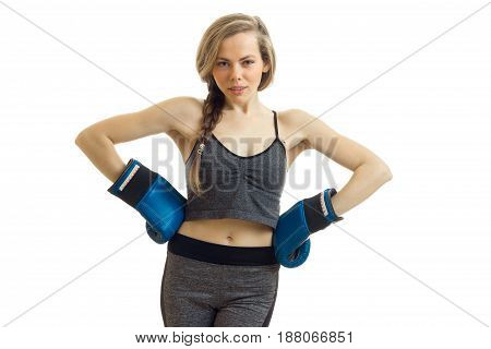 sexy young athletic blonde looks straight and keeps hands on the sides in boxing gloves is isolated on a white background