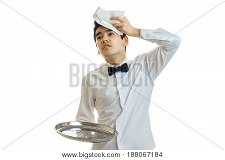 the young weary waiter holding a tray is empty and put on the head of a towel isolated on white background