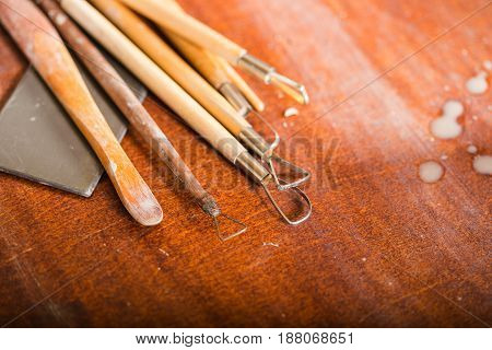 pottery, workshop, ceramics art concept - closeup on sculpting tools set on wooden table, clay stacks, different profiles, cutters for carving shapes