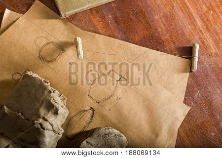 potter, clay workshop, ceramics art concept - closeup on two parts of the clay piece is cut with string cutter, raw fireclay and pencil drawing of jugs on wooden table, tools set, flat lay
