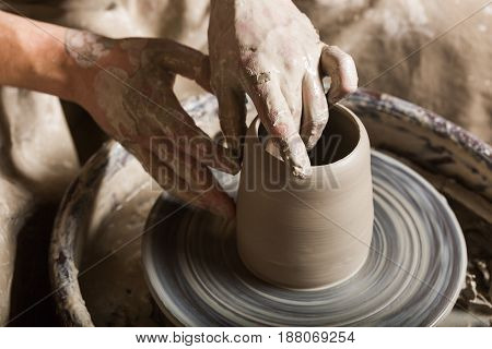 pottery, workshop, ceramics art concept - closeup on male hands sculpt some new utensil with fingers and water, man hands works with potter's wheel and raw fireclay, top view