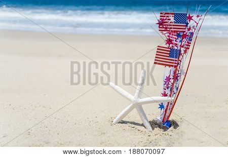 Patriotic USA background with starfish amd decorations on the sandy beach