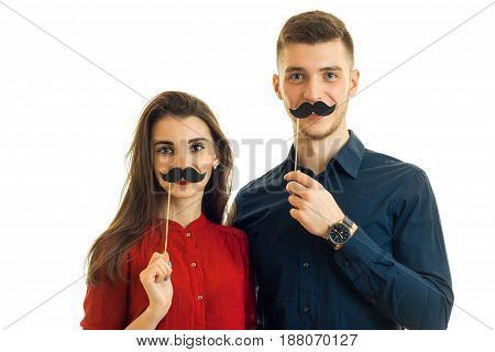 cheerful young couple having fun with a paper mustache isolated on white background