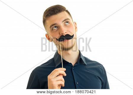 Portrait of a guy with a paper mustache isolated on white background
