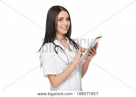Positivity and happy young female doctor in white, smiling at camera, using tablet, reading about patient, press at screen, choosing something. High technology of modern medicine at hospital. Isolate.