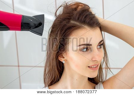 a girl dries hair in the bathroom in fron of mirror