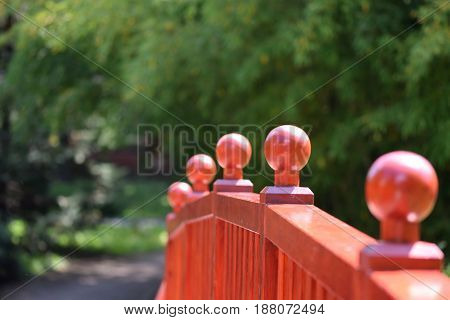 Light brown bridge wooden fence with wooden balls and the bockeh green path background