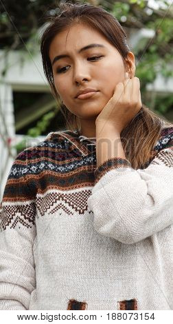 Youthful Peruvian Youngster And Loneliness Wearing a Knit Sweater