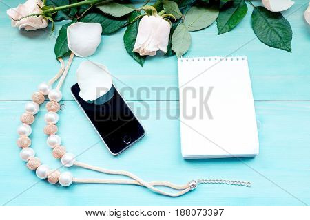 Spring background layout on a blue wooden background with flowers and rose petals Notepad sheets for notes and purse and beads accessories