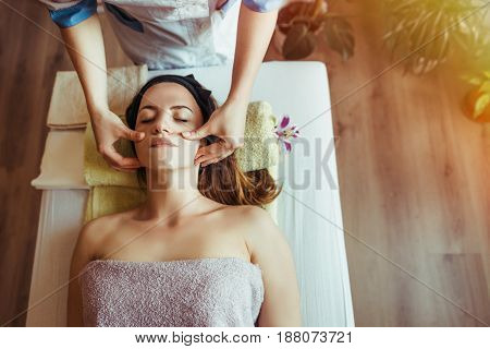 Lifting face massage with sugar gel. Beautiful young woman getting a face treatment at beauty salon.