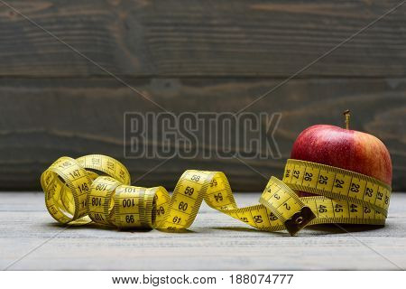 Tape For Measuring Wraps Around Apple On Vintage Wooden Background