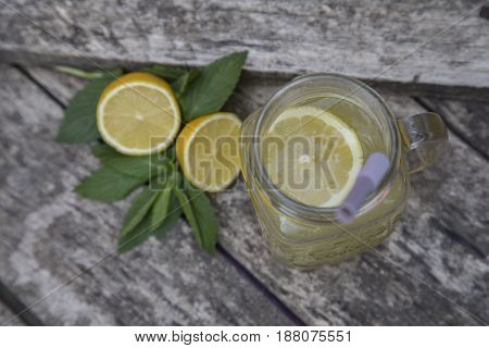 Lemon juice in jar decorated with fresh lemons and mint leaves.