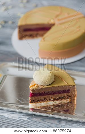 Bakery with piece of unusual yellow mousse cake with almond dacquoise, raspberry confit, crispy layer with caramelized hazelnuts and raspberry powder, mousse based on bitter chocolate served on wooden table.