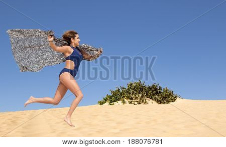 Pretty young brunette with a scarf running in the dunes