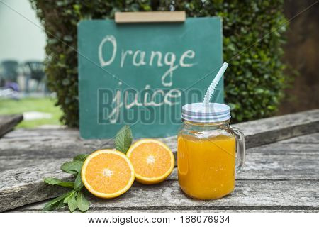 Orange juice in jar decorated with fresh oranges and mint leaves.